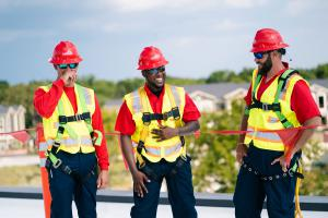 Capturing photo of AD Khrone leading roofing team members atop a commercial roof.